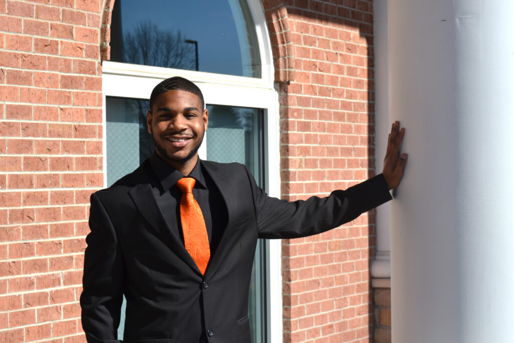 student in a suit and tie smiling