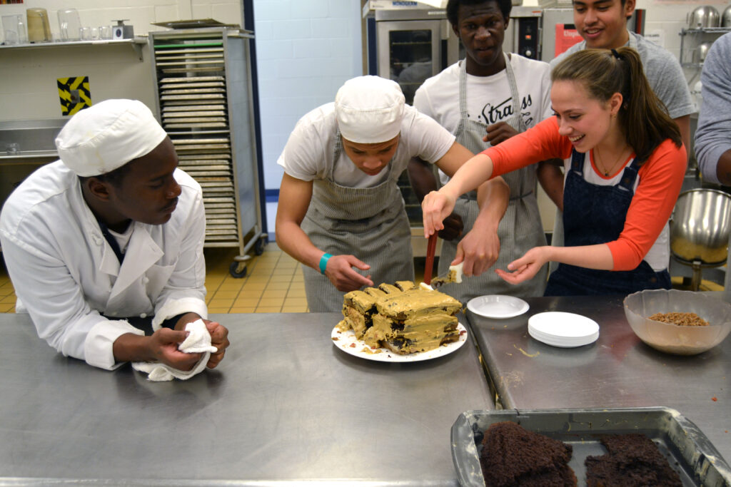 culinary students cutting into a cake